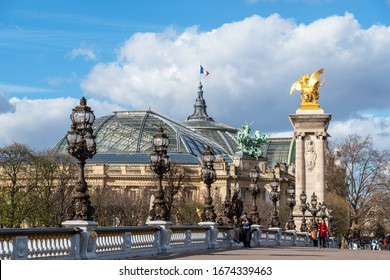 Paris, France - March 13 2020: Golden statue and lanterns of Pont Alexandre III bridge with Grand Palais and French flag waving on top of the building - Paris, France