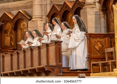 Paris, France - March 14, 2018: Nuns praying inside The Basilica of the Sacred Heart of Paris, is a Roman Catholic church and minor basilica, dedicated to the Sacred Heart of Jesus
