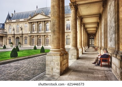 PARIS, FRANCE - MARCH 15 2008: Elderly man reading a book in musee des Archives nationales (Musee de l'Histoire de France), hotel de Soubise.