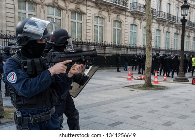"Paris, FRANCE - March, 16 2019 : Policeman from anti riot unit with a LBD flashball, control protesters yellow vests ""Gilets Jaunes"" at Paris on Champs Elysees."