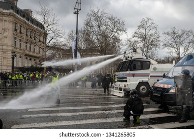 "Paris, FRANCE - March, 16 2019 : Policemens from anti riot unit with a water canon truck try to control protesters yellow vests ""Gilets Jaunes"" at Paris on Champs Elysees."
