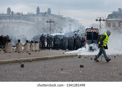 "Paris, FRANCE - March, 16 2019 : Policemens from anti riot unit try to control protesters yellow vests ""Gilets Jaunes"" at Paris on Champs Elysees."