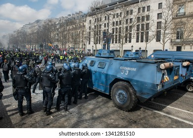 "Paris, FRANCE - March, 16 2019 : Anti riot policeman with a VBRG an armoured vehicle used by the gendarmerie as an Internal security vehicle during the riots of the yellow vests ""gilets jaunes""."