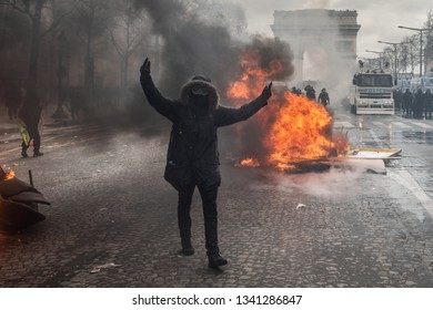 "Paris, FRANCE - March, 16 2019 : Protesters burning urban furnitures and provoke police forces during a demonstration of yellow vests ""Gilets Jaunes"" at Paris on Champs Elysees."