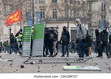 "Paris, FRANCE - March, 16 2019 : Protesters yellow vests ""Gilets Jaunes"" attack police from anti riot unit during a demonstration at Paris on Champs Elysees."