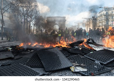 """Paris, FRANCE - March, 16 2019 : Protesters yellow vests """"Gilets Jaunes"""" burnig urban furnitures during a demonstration at Paris on Champs Elysees."""