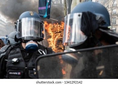 """Paris, FRANCE - March, 16 2019 : Policemens from anti riot unit in front of  newspaper kiosk bruning during a demonstration of protesters yellow vests """"Gilets Jaunes"""" at Paris on Champs Elysees."""