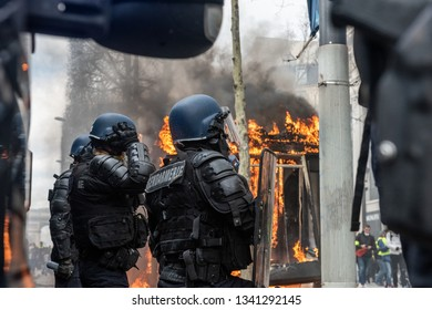 "Paris, FRANCE - March, 16 2019 : Policemens from anti riot unit in front of  newspaper kiosk bruning during a demonstration of protesters yellow vests ""Gilets Jaunes"" at Paris on Champs Elysees."