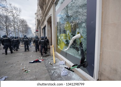 """Paris, FRANCE - March, 16 2019 : Policemens from anti riot unit beside   a shop window vandalized during a demonstration of yellow vest """"Gilets jaunes"""" on Champs Elysees at Paris."""