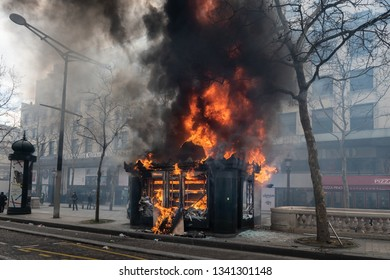 """Paris, FRANCE - March, 16 2019 : A  newspaper kiosk bruning during a demonstration of protesters yellow vests """"Gilets Jaunes"""" at Paris on Champs Elysees."""