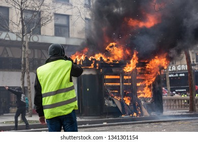 "Paris, FRANCE - March, 16 2019 : A  newspaper kiosk bruning during a demonstration of protesters yellow vests ""Gilets Jaunes"" at Paris on Champs Elysees."