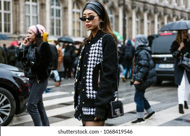 PARIS, FRANCE - MARCH 2, 2018:  Aimee Song wears a black and white tweed jacket, black thigh high leather boots, sunglasses, outside BALMAIN show at Paris Fashion Week FW'18-19