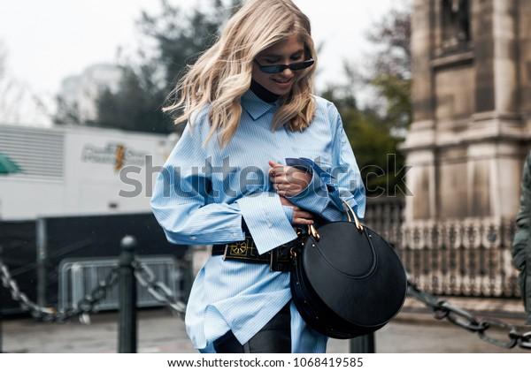 PARIS, FRANCE - MARCH 2, 2018: Xenia Van Der Woodsen wears a blue shirt, a bag, a belt, sunglasses, red thigh high boots, outside BALMAIN show at Paris Fashion Week FW'18-19