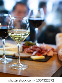 Paris / France - March, 2, 2019: Paris, bar called L'Excuse in the center of the city near Chatlet metro station. Aperitif, wine degustation, three glasses with red and white wine, cheese, bread, ham