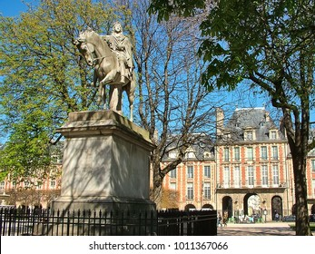 Paris, France - March 20, 2014: Monument to Louis 13th in the ancient Parisian Place des Vosges in the Marais. The beginning of spring.
