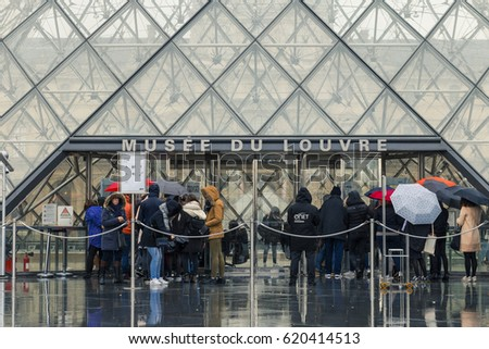 Paris, France - MARCH 2017. People waiting in a queue for entering the Louvre Museum. Tourists walking with their umbrellas in the central courtyard of the famous art museum on a rainy day. Toned