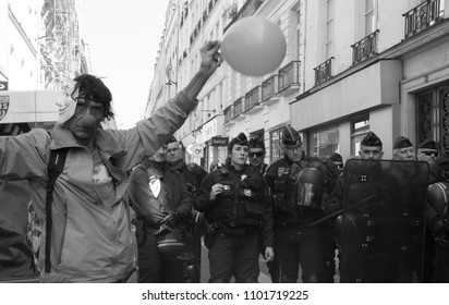 Paris, France - March 2018: A protestor dressed up as a clown with a balloon stands next to French riot police