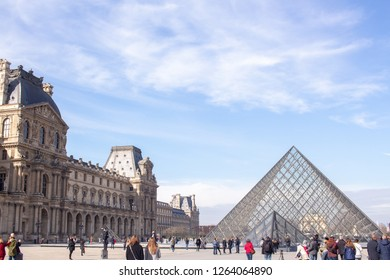 PARIS, FRANCE - March 2018: Tourists around Louvre Museum's Pyramid