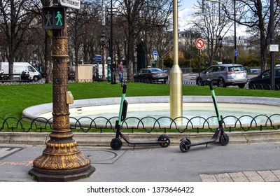 Paris, France - March 2019: Some of the popular electric rental scooters parked next to small roundabout with fountain and green light in Paris, France -Image
