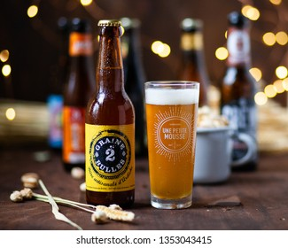 Paris / France - March, 22, 2019: craft french beer, glass and fruit basket. Text on bottle: Seed 2 Bubbles. Craft beer from Ardeche. 227 Jules Romains street. Text on glass: a little moss. Brewery