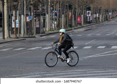 PARIS, FRANCE March 22th 2020 : The Cyclist with medical mask on Champs Elysées empty during the period of containment measures  due to the Covid-19 Coronavirus.