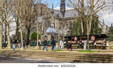Paris, France - March 24, 2014: Passers-by walking along the shops of second-hand booksellers along the Montebello promenade ( Quai de Montebello) against the background of Notre Dame de Paris.