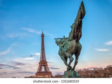 Paris, France - March 26, 2019: France Reborn Statue on Pont de Bir-Hakeim at Golden hour with Eiffel tower in background.