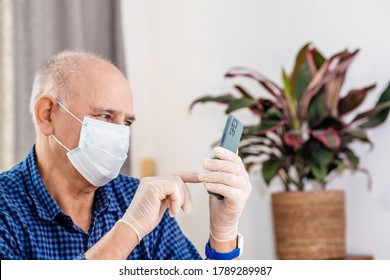 Paris, France - March 26, 2020: Side view of a senior optimistic man touching with finger on the latest smartphone telephone wearing protective gloves and surgical mask during COVID-19 coronavirus