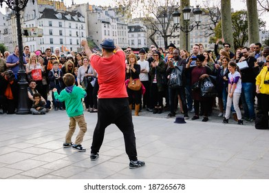 PARIS, FRANCE - MARCH 29, 2014: Unidentified young man dances breakdance with unidentified boy that he invited from the public on street. Dozens artists perform on the streets and in metro of Paris.