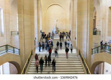 Paris, France - March 31, 2019: People on stairs look at The Winged Victory of Samothrace.