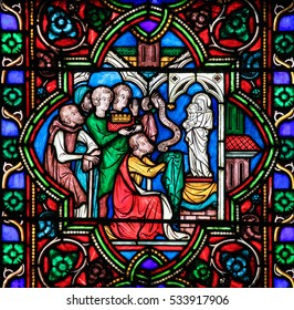 PARIS, FRANCE - MARCH 4, 2011: Stained Glass in Notre Dame Cathedral of Paris depicting Charles II (the Bald), grandson of Charlemagne, kneeling before the Virgin Mary.