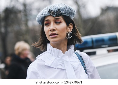 Paris, France - March 5, 2019: Woman wearing wearing a white shirt, light blue pants, black heels, light blue hat and printed Chanel bag, before a fashion show during Paris Fashion Week - PFWFW19