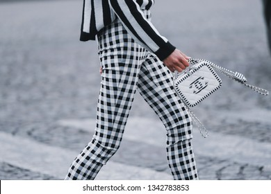 Paris, France - March 5, 2019: Street style - Woman wearing black white striped jumper, plaid pants and Chanel bag,  before a fashion show during Paris Fashion Week - PFWFW19