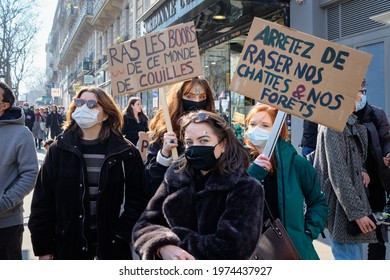 PARIS, FRANCE - MARCH, 8, 2021: Young women posing with funny signs on cardboards and masks against Covid-19 at the feminist march and protest in Paris on March 8, International Women's Day
