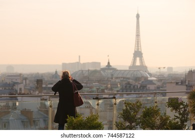 Paris, France - Mars 16, 2016 : Woman taking the Eiffel tower in photo from an elevated point of view in Paris.