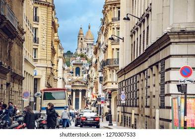 Paris, France - May 08, 2017: City life on Rue Laffitte with view of Eglise Notre-Dame de Lorette and Sacre-Cœur basilica on Monmartre hill in Paris, France