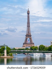 Paris, France - May 08 2020: French flag waving in the middle of the Eiffel Tower during coronavirus lockdown at President Macron request