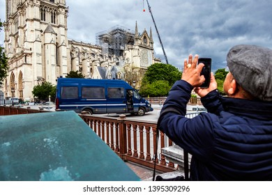 PARIS, FRANCE - MAY 09, 2019. Notre Dame de Paris, phase of verification and consolidation of the walls. A tourist takes pictures of the cathedral and a police car with his smarphone.