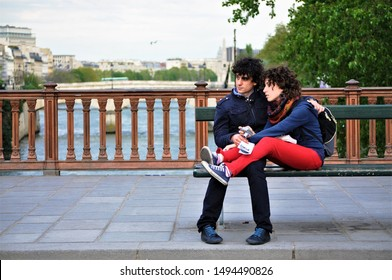 Paris, France - May 1 2010: a Paris couple snuggle on a bench outside of Notre Dame cathedral watching passers by with the River Seine in the background