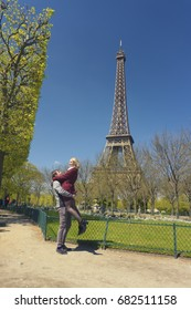 PARIS, FRANCE - MAY 1, 2016: Young couple just got engaged in front of the Eiffel Tower, Champ de Mars, Paris, France. The man is lifting up his fiancee in a spring day. They look very happy.