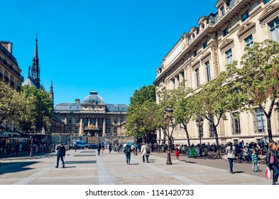 Paris, France - May 10, 2017: People on the square of Louis Lepine with view of the chapel of Saint-Chapelle and Palais de Justice. Paris, France