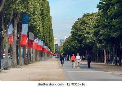 Paris, France - May 10, 2017: People walk down the Champs Elysees with French flags on trees waving celebrating national holliday in Paris, France