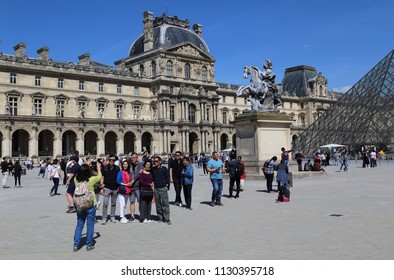 Paris, France - May 11, 2018: Tourists take pictures on the courtyard of the Louvre museum in Paris, France on May 11, 2018