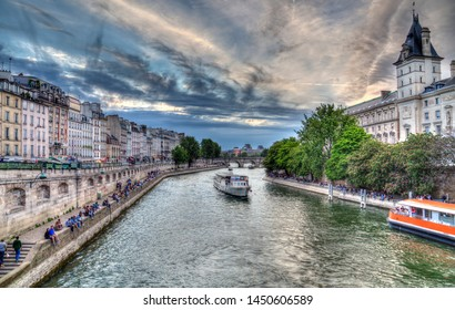 Paris, France - May 11, 2018: Boat with tourists sails past historical buildings and people sitting on the bank of the river Seine in Paris, France on May 11, 2018