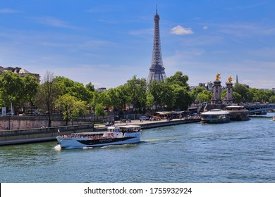 Paris, France - May 11, 2018: Boat with tourists sails on the river Seine past the Eiffel Tower in Paris, France on May 11, 2018