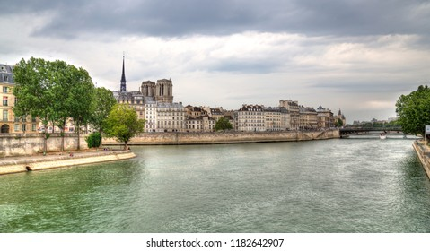 Paris, France - May 12, 2018: Historical buildings including the towers of the Notre Dame and people sitting on the banks of the Seine river in Paris, France on May 12, 2018