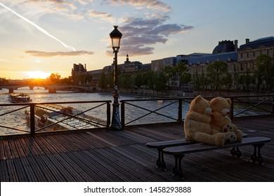 Paris, France - May 12, 2019: 2 teddy bear on bench on Pont des arts bridge in Paris