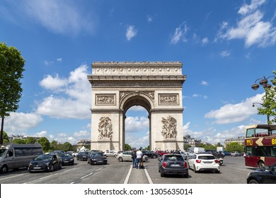 Paris, France - May 13, 2017: Famous Arc de Triomphe against a blue sky with cars in front of it. The Arc de Triomphe is one of the most famous monuments in Paris.
