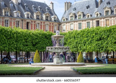 Paris, France - May 13, 2017: People around a fountain on place des vosges