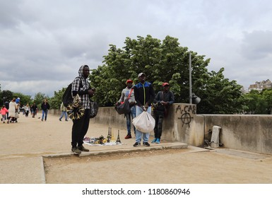 Paris, France - May 13, 2018: African souvenir sellers with their wares near the Eifel tower in Paris, France on May 13, 2018